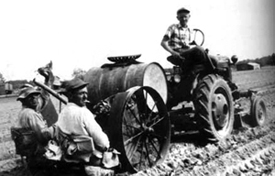 Ross Joseph Nichols and Louis Vann transplant tobacoo on the Nichols farm in the Roanoke-Chowan area of North Carolina.  The planter was originally pulled by mules, but the mules have been replaced by the tractor.  This one is driven by Fred Nichols.  Photo by the Nichols family.