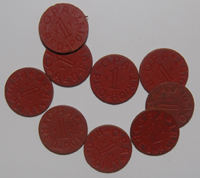 These red cardboard discs are one half inch in diameter and about one sixteenth of an inch thick.